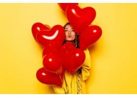 穿着黄色毛衣的女孩微笑着亲吻从一堆红色_259371901