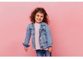 粉色背景上站着一头卷发面带微笑的小女孩_1243199001