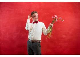 红色工作室背景上拿着鲜花的年轻漂亮男子_1012875901