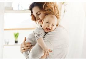 快乐的年轻妈妈抱着珍贵的小孩子温柔地拥_881160901