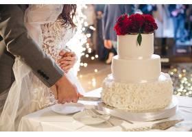 快乐的新娘和新郎切了一个婚礼蛋糕_456744301