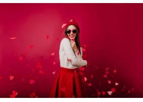 情绪激动的年轻女子戴着红帽子和墨镜站在派_1108383801