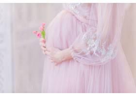 身着鲜艳粉色连衣裙的美丽孕妇手牵手摆腹部_261272601