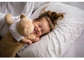 躺在床上的小女孩抱着柔软的玩具带着孩_904584801