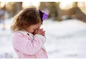 阳光下小女孩在白雪覆盖的花园里祈祷距_1194280001