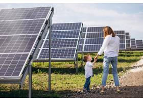 母亲和她的小儿子在太阳能电池板旁_517578901