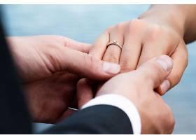 灯光下新郎把戒指戴在新娘手指上的特写_1007354601