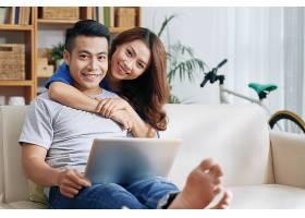 亚洲男人在沙发上放松家里有笔记本电脑_557742301