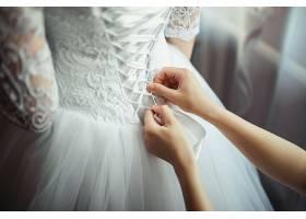 伴娘在新娘婚纱背面打蝴蝶结_245501701