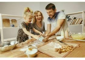 可爱的小女孩和她漂亮的父母在家里的厨房里_1116109701