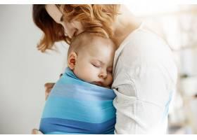可爱的小男婴白天穿着蓝色的婴儿吊带躺在妈_881169201
