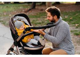 大自然中坐在户外婴儿车里的爸爸和孩子_1190468401