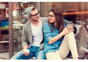 在咖啡馆外喝着咖啡放松的年轻人_1089615701