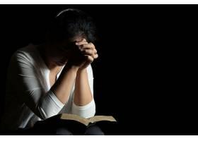 在教堂里双手交叉在一本圣经上祈祷_550782001