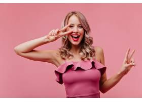 滿意的女士留著浪漫的發型在粉色墻上大_1230538301