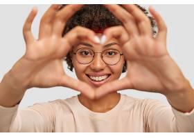 迷人的年轻女子的照片让心形的手势盖过了脸_1208694201
