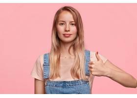 迷人自信的年輕女模特豎起大拇指的照片_1208630601