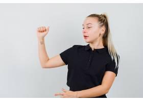 金发女士举起手臂指着身着黑色T恤的侧面_1249648601