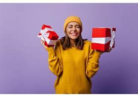 熱情的戴著針織帽的女士拿著圣誕禮物擺姿勢_1215224101