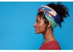 站在蓝色的墙上年轻迷人的黑发女子站在蓝_1247165501