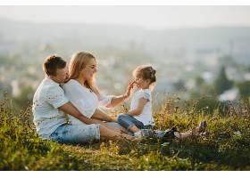 美丽的夏日幸福的父母和他们的小女儿在草_291396501