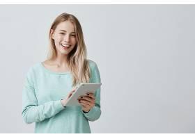 美丽的女性留着金色的长发使用平板电脑_911697201