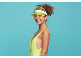 年轻可爱的卷发女性穿着泳衣站在蓝色背景上_1258370201