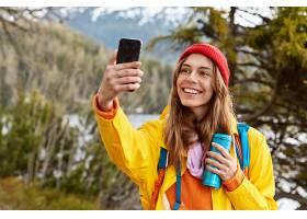开心可爱的黑发女孩用手机自拍穿着雨衣_1163175701
