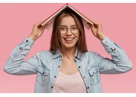快乐可爱的年轻女子将书举过头顶温柔地微_1220480701