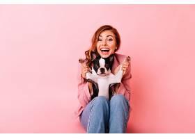 快乐的女孩穿着牛仔裤和有趣的小狗玩耍激_1193472301