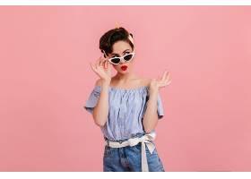 戴着墨镜的沉思的美女站在粉色的背景上摄_1243013301