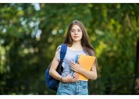 快乐迷人的年轻女子背着背包和笔记本站在公_1104595901