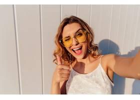 戴着黄色眼镜的迷人微笑女孩眨着眼睛竖起大_259368401