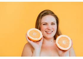 曲线美的金发女子拿着两个新鲜橙子_346968501