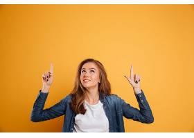 一幅可爱的微笑女孩的肖像两个手指向上指_681940401