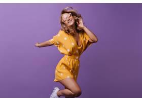 令人驚嘆的卷曲女模特跳上紫色身穿亮黃色_1193339601