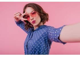 化妆亮丽的可爱女子在粉色墙上自拍脸上带_1065839801