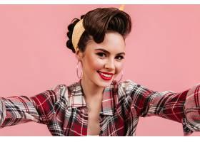 可爱的年轻女子穿着格子衬衫在粉色背景上_1243011801
