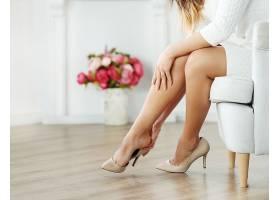 坐在扶手椅上的女人穿着米色高跟鞋_755405901