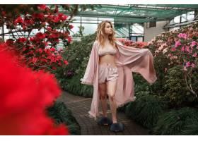 美丽性感的女孩穿着粉色浴袍和内衣站在花园_334137001