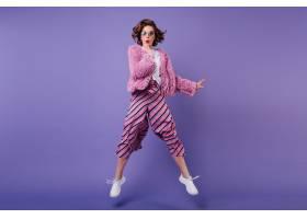 身着条纹长裤的卷发女子在紫色墙上跳来跳去_1065790301