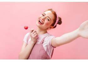 身穿粉色连体裤和白色上衣的快乐女子手持糖_1267797301