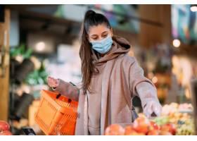 戴着防护口罩的年轻女子在购物_1254138201
