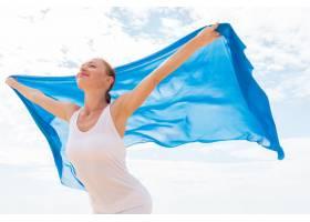 戴着飘逸的蓝色围巾的年轻女子_115325001