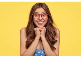 戴着眼镜在黄色墙上摆姿势的可爱的年轻女子_1113747701