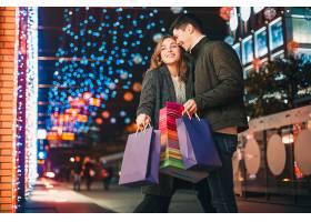 提着购物袋的幸福夫妇在城市里享受夜晚_915943701