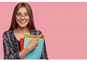 摄影棚拍摄的英俊年轻女商人戴着眼镜在粉色_1114247801