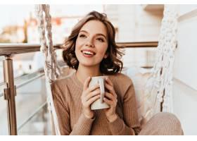 无忧无虑的棕妆女孩在阳台喝茶可爱的黑发_1201644401
