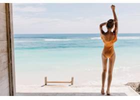 早上穿着橙色泳衣的赤脚女孩望着大海晒_1136645901