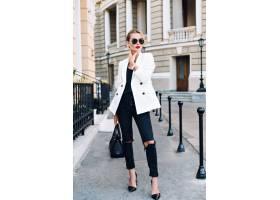 时装模特穿着高跟鞋走在街上她戴着墨镜_1005596301